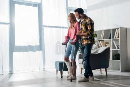 bearded man looking at injured woman holding crutches at home