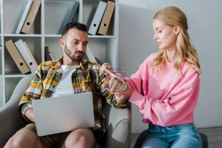 Photo pour Femme soignante pansant la main blessée d'un homme barbu assis avec un ordinateur portable - image libre de droit