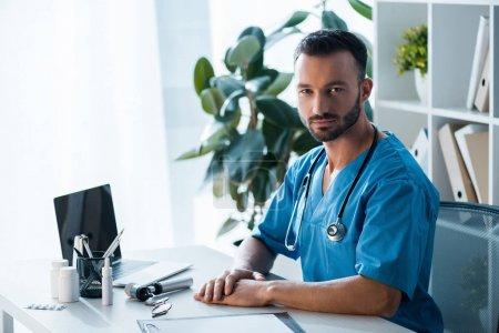 Photo pour Beau médecin barbu regardant la caméra près d'un ordinateur portable dans la clinique - image libre de droit