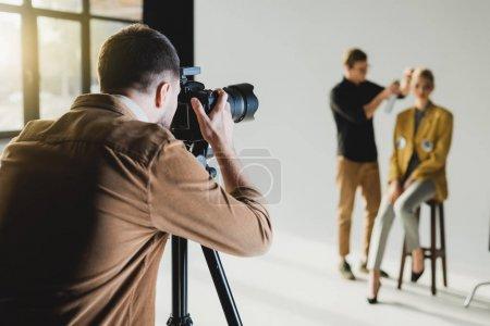 Photo pour Focus sélectif du photographe photographiant le modèle et le coiffeur - image libre de droit