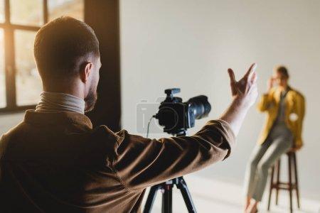 Photo pour Foyer sélectif du photographe pointant avec la main et en regardant le modèle - image libre de droit