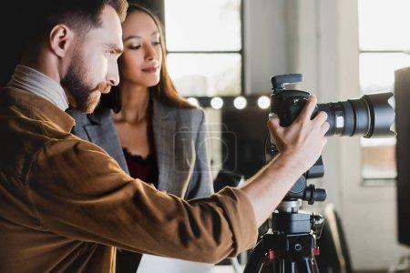 Photo pour Producteur et photographe prenant des photos avec un appareil photo numérique dans les coulisses - image libre de droit