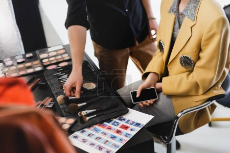 Photo for Cropped view of Makeup Artist taking cosmetic brush and model holding smartphone on backstage - Royalty Free Image