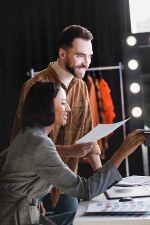 Photo pour Producteur souriant et photographe regardant loin sur les coulisses - image libre de droit
