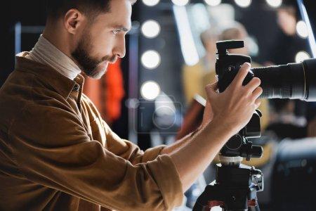 Photo pour Vue latérale du photographe prenant des photos avec appareil photo numérique dans les coulisses - image libre de droit