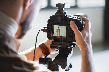 Photo pour Vue recadrée du photographe prenant des photos avec appareil photo numérique dans les coulisses - image libre de droit