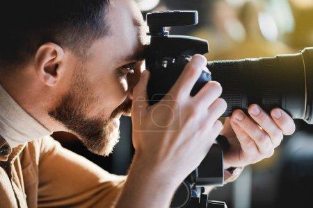 Photo pour Vue latérale d'un photographe souriant prenant une photo avec un appareil photo numérique dans les coulisses - image libre de droit