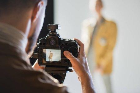 Photo pour Focus sélectif du photographe photographiant le modèle avec l'appareil photo numérique dans les coulisses - image libre de droit
