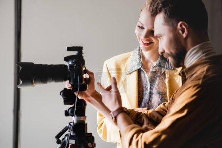 Photo pour Photographe et modèle souriant regardant l'appareil photo numérique dans les coulisses - image libre de droit
