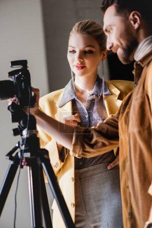 Photo pour Photographe souriant et modèle regardant l'appareil photo numérique dans les coulisses - image libre de droit