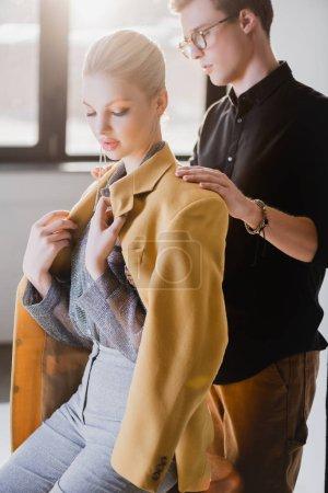 Photo pour Beau styliste portant une veste sur un modèle élégant dans les coulisses - image libre de droit
