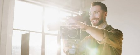 Photo for Panoramic shot of smiling photographer taking photo with digital camera and pointing with finger on backstage - Royalty Free Image