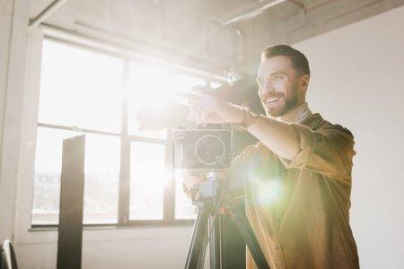 Photo pour Photographe souriant prenant des photos avec appareil photo numérique et pointant du doigt sur les coulisses - image libre de droit