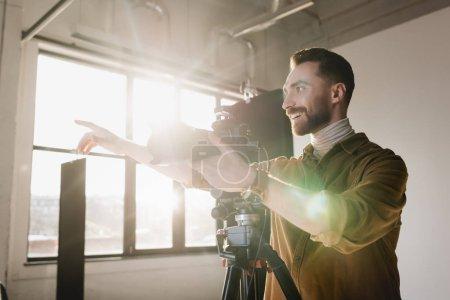Foto de Fotógrafo sonriente tomando fotos con cámara digital y señalando con el dedo en el backstage - Imagen libre de derechos