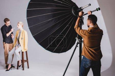 Photo pour Foyer sélectif du photographe touchant réflecteur sur les coulisses et maquilleur faisant maquillage au modèle - image libre de droit