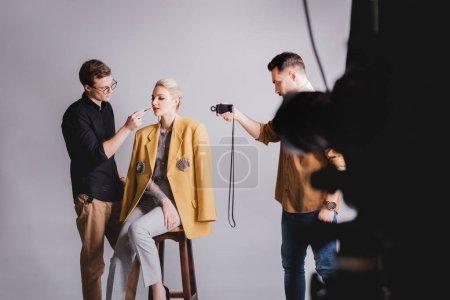Photo pour Focus sélectif du photographe filmant comment maquillage Artiste de maquillage maquillage à modèle élégant - image libre de droit