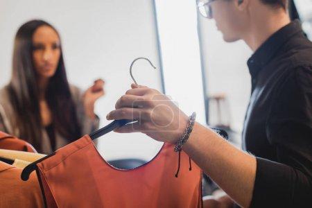 Photo pour Foyer sélectif du styliste montrant des vêtements au producteur sur les coulisses - image libre de droit