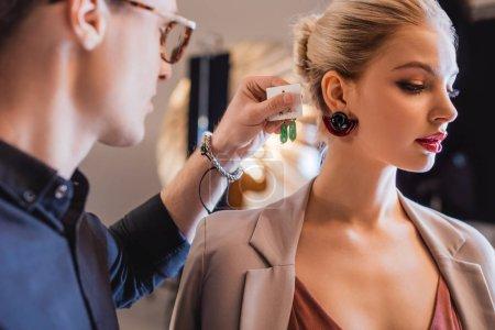 Photo pour Foyer sélectif du styliste choisir des boucles d'oreilles pour modèle élégant sur les coulisses - image libre de droit