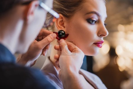 Photo pour Crochet du styliste mettant la boucle d'oreille sur le modèle dans les coulisses - image libre de droit