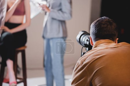 Photo pour Foyer sélectif du photographe prenant la photo du modèle et coiffeur - image libre de droit