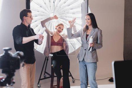 Photo pour Un accent sélectif de modèle souriant, styliste, coiffeur montrant oui geste sur les coulisses - image libre de droit