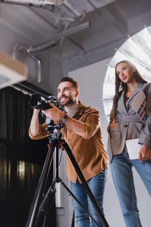 Photo for Low angle view of smiling photographer taking photo and producer looking away on backstage - Royalty Free Image