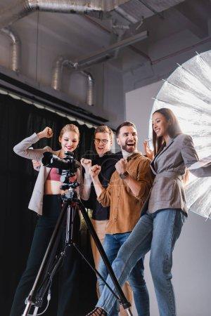 Photo pour Vue à faible angle du photographe souriant, du modèle, du styliste et du producteur regardant l'appareil photo numérique et montrant un geste oui dans les coulisses - image libre de droit