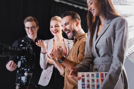 Photo for Smiling photographer, model, stylist and producer looking at digital camera on backstage - Royalty Free Image