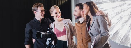 panoramic shot of smiling photographer, model, stylist and producer hugging on backstage