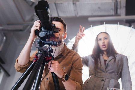 Tiefansicht des Fotografen beim Fotografieren und des Produzenten, der mit dem Finger auf Backstage zeigt