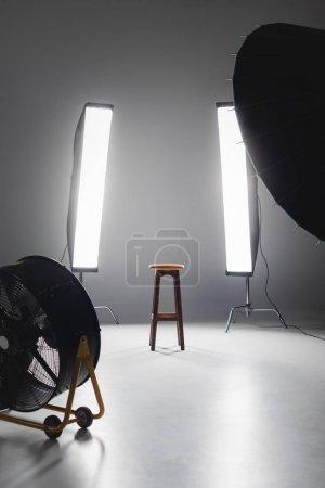 Photo pour Ventilateur, réflecteur, tabouret en bois et lumières dans les coulisses du studio photo - image libre de droit