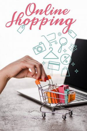 Photo pour Cropped view of woman holding toy shopping cart near laptop near online shopping letters on white, e-commerce concept - image libre de droit