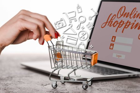 Photo for Cropped view of woman holding toy shopping cart near laptop with illustration on white, e-commerce concept - Royalty Free Image