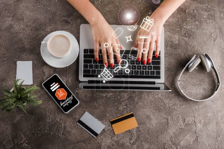 top view of woman using laptop near smartphone, cup of coffee, plant, headphones credit cards and illustration, e-commerce concept