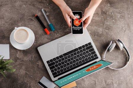 Photo pour Vue du dessus de la femme tenant smartphone avec des lettres d'achat en ligne près de l'ordinateur portable, tasse de café, plante, écouteurs et cartes de crédit, concept de commerce électronique - image libre de droit