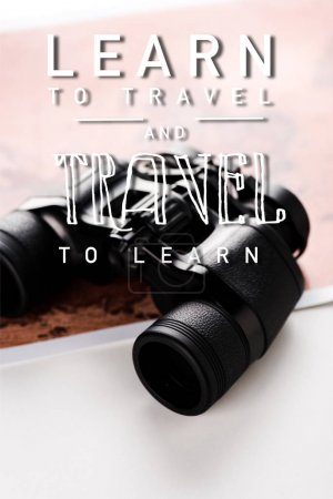 Photo for Selective focus of binoculars near map and learn to travel and travel to learn letters on white - Royalty Free Image