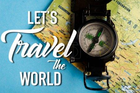 Photo pour Vue du dessus de la boussole noire sur la carte proche permet de voyager les lettres du monde sur bleu - image libre de droit