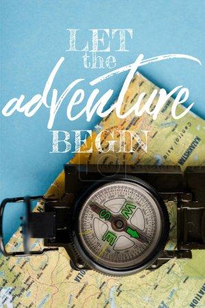 Foto de Vista superior de la brújula negra en el mapa cerca de dejar que la aventura comience las letras en azul. - Imagen libre de derechos