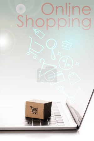 toy box on laptop keyboard near illustration and online shopping letters on white, e-commerce concept