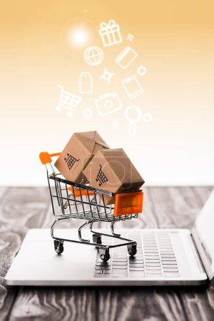 Photo for Selective focus of toy shopping cart with small carton boxes on laptop keyboard near illustration on orange, e-commerce concept - Royalty Free Image
