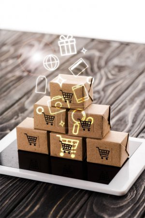 toy carton boxes on digital tablet near illustration, e-commerce concept