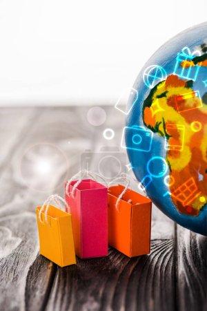 Photo pour Sacs jouets près du globe sur la table avec illustration isolée sur blanc, concept de commerce électronique - image libre de droit