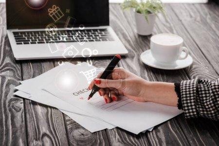 Photo pour Vue recadrée d'une femme d'affaires tenant un stylo marqueur rouge près de la liste de contrôle, illustration, tasse et ordinateur portable sur la table, concept de commerce électronique - image libre de droit