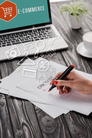 cropped view of businesswoman holding red marker pen near checklist, illustration, cup and laptop with e-commerce letters