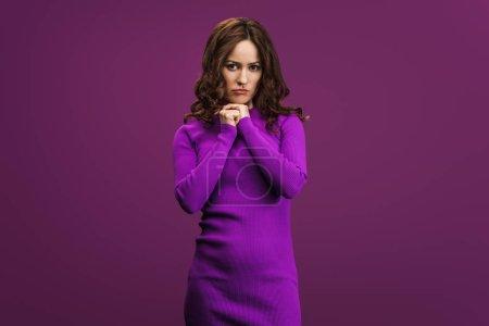 Photo pour Femme bouleversée debout avec les mains serrées et regardant la caméra sur fond violet - image libre de droit