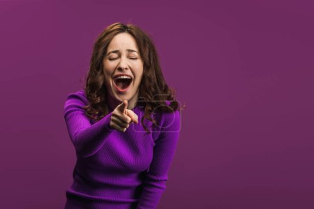 Photo for Cheerful woman laughing with closed eyes and pointing with finger at camera on purple background - Royalty Free Image