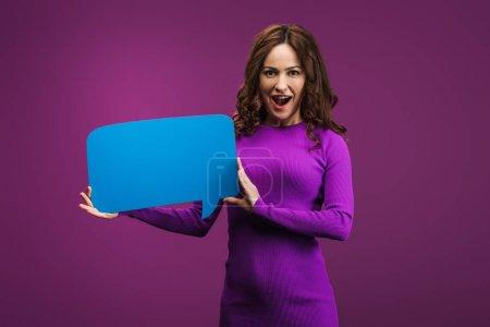 Photo pour Excité femme tenant parole bulle sur fond violet - image libre de droit