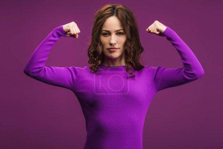 Foto de Chica confiada demostrando poder sobre fondo púrpura - Imagen libre de derechos