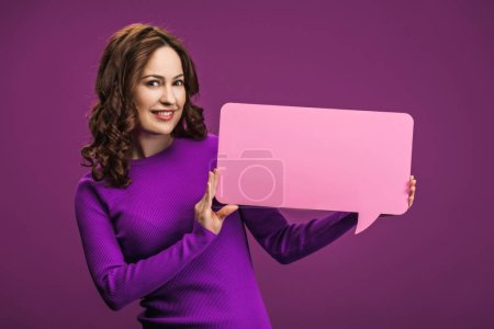 Photo for Smiling woman holding speech bubble on purple background - Royalty Free Image