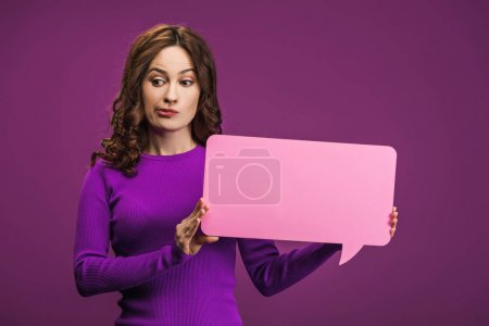 Photo for Skeptical woman holding speech bubble on purple background - Royalty Free Image